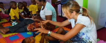 Projects Abroad Intern doing stretches with local children during her occupational therapy internship in Tanzania.
